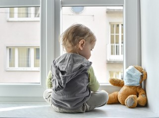 Child in home quarantine standing at the window with his sick teddy bear wearing a medical mask against viruses during coronavirus and flu outbreak. Children and illness COVID-2019 disease concept